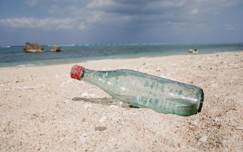 Abandoned bottle on shore at beach against sky