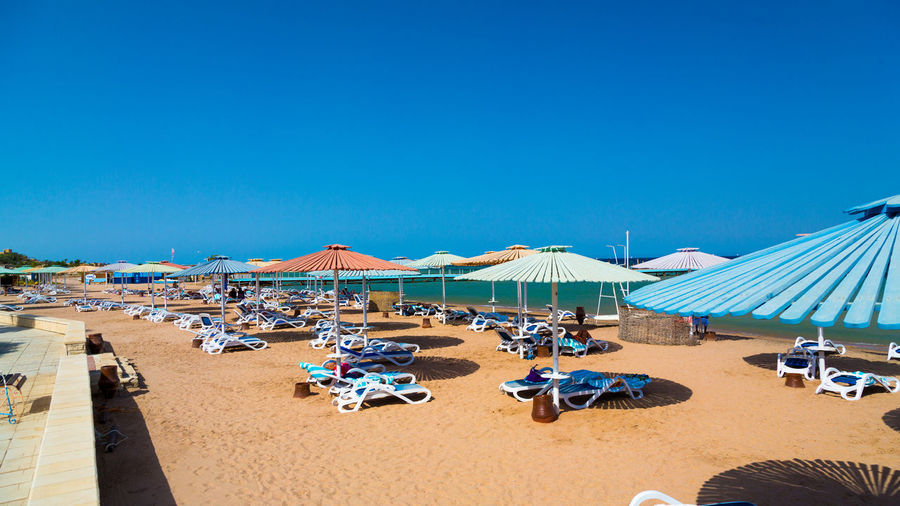 Sun loungers with canopies in row at beach