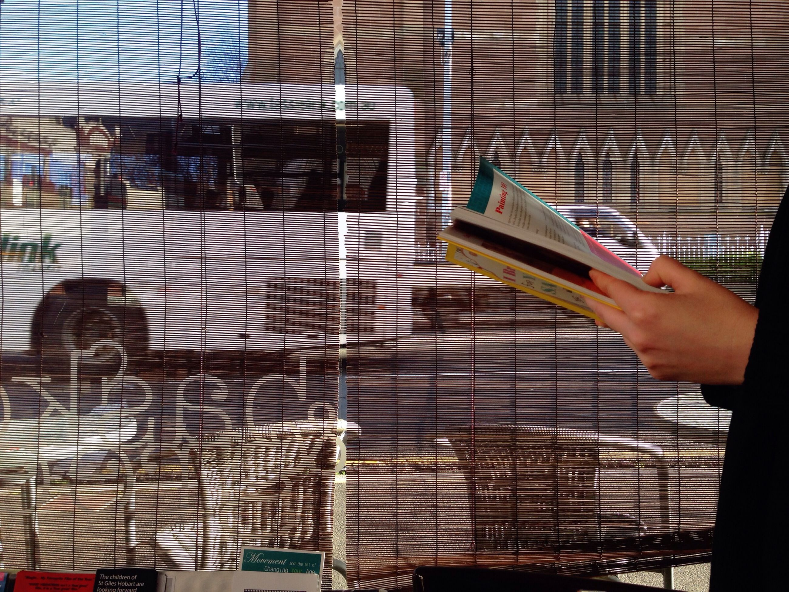 indoors, person, lifestyles, part of, cropped, men, leisure activity, glass - material, built structure, architecture, unrecognizable person, holding, reflection, railing, window, day