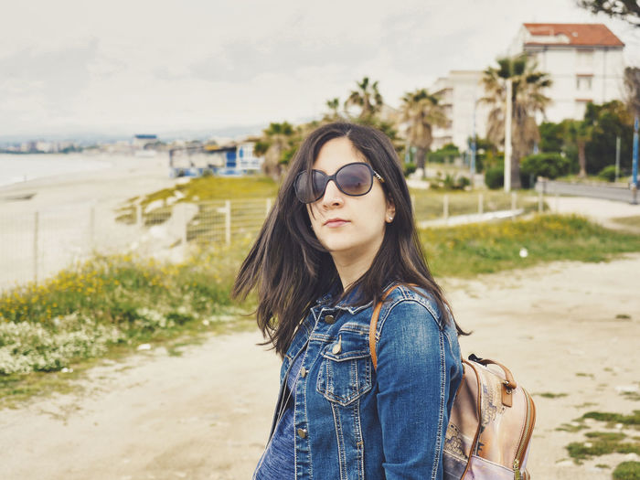 Portrait of young woman wearing sunglasses while standing at beach