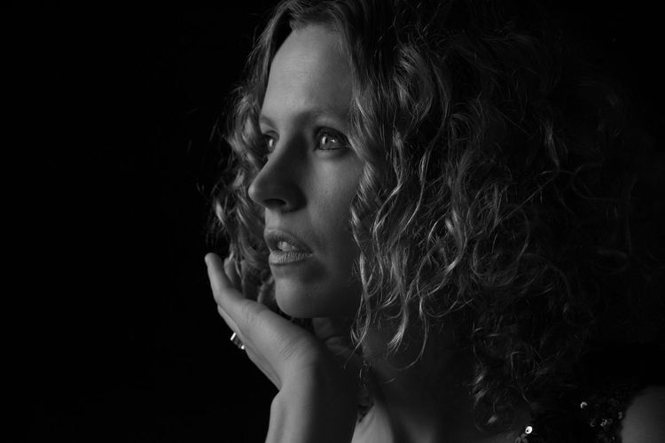 Close-Up Of Contemplated Young Woman Against Black Background