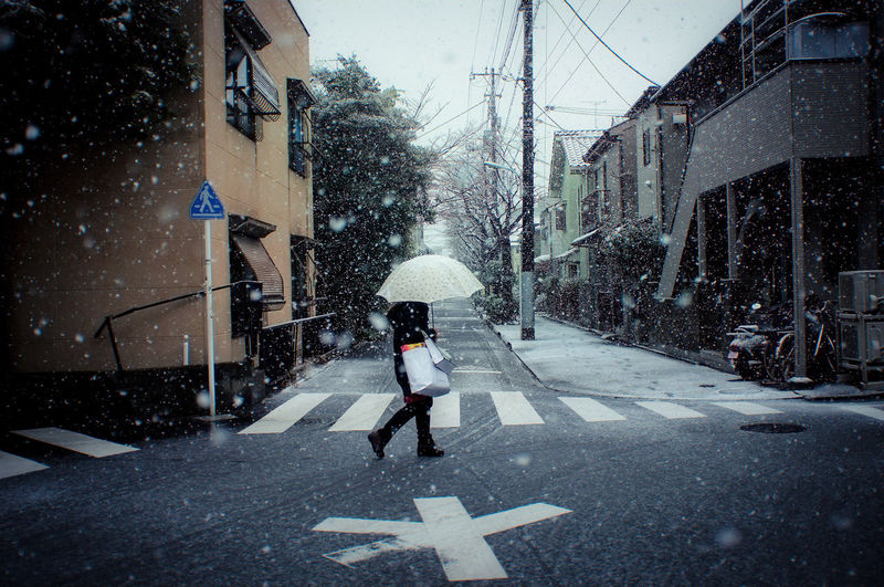 Woman walking with shopping bags and umbrella on street during snowfall
