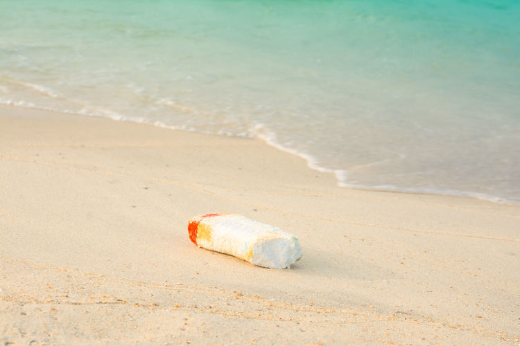 Abandoned bottle on sand at beach