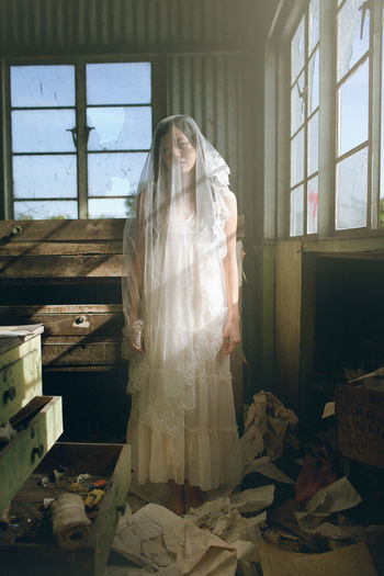 Beautiful sad girl alone with veil on. The Portraitist - 2018 EyeEm Awards Portrait Of A Woman Sunlight Beautiful Woman Deserted Females Grunge Hairstyle Indoors  Lifestyles Long Hair Portrait Shadow Veil Window Women Young Adult Young Women