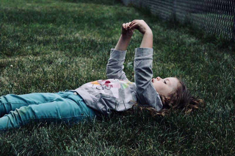 Girl lying on grassy field