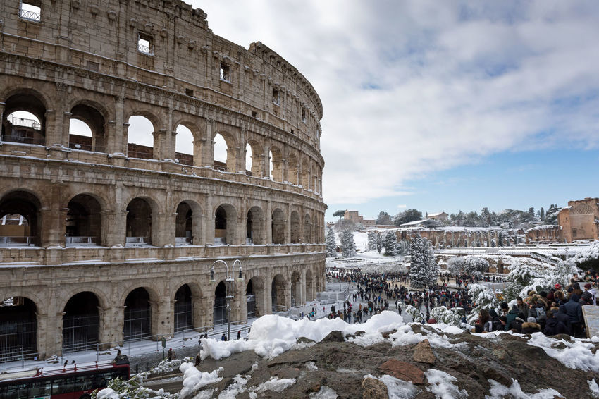 Rome, Italy - February 26, 2018: An exceptional weather event causes a cold and cold air across Europe, including Italy. Snow comes in the capital, covering streets and monuments of a white white coat. In the picture, Colosseo comes alive with hundreds of people who went out to celebrate the event. Snowy Ancient Ancient Civilization Arch Architecture Building Exterior Built Structure Buran Climatic Event Cloud - Sky Cold Cold Temperature Day History Large Group Of People Low Angle View Old Ruin Outdoors Sky Snow Tourism Travel Travel Destinations