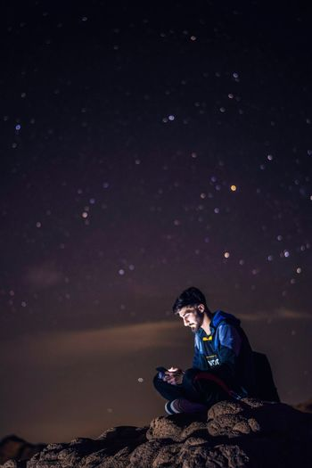 Young Man Using Phone While Sitting On Rock Against Star Field