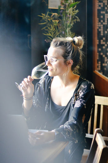 Young Woman Drinking Alcohol In Restaurant