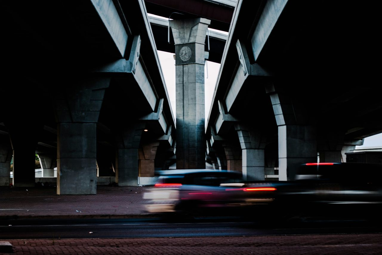 Blurred motion of cars moving on road below bridge
