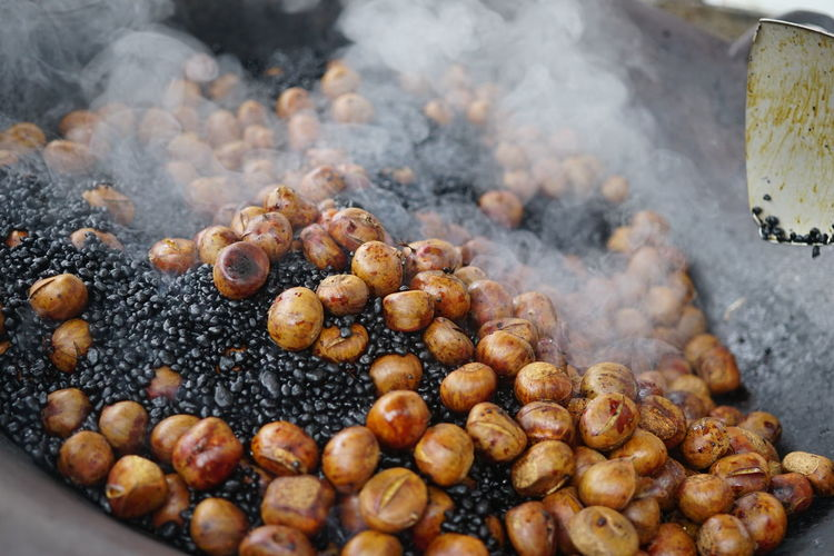 Roasted Chestnut on a pan with smoke. Street Food Food And Drink Food Freshness Smoke - Physical Structure Heat - Temperature Large Group Of Objects Steam Wellbeing Preparation  Abundance Healthy Eating No People Close-up Burning Snack Kitchen Utensil Roasted Nut Day Nut - Food