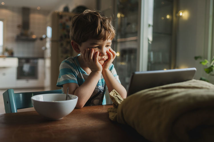 Boy looking away while sitting on table at home