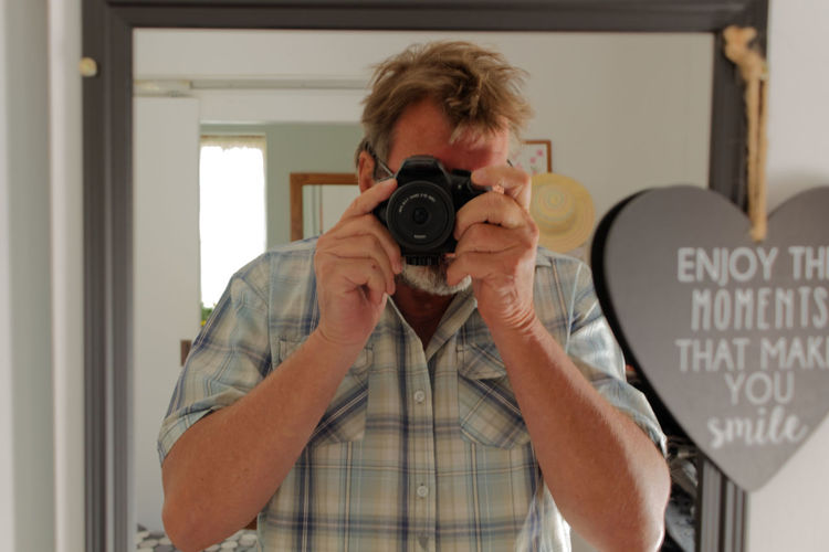 Portrait of man reflecting while photographing on mirror