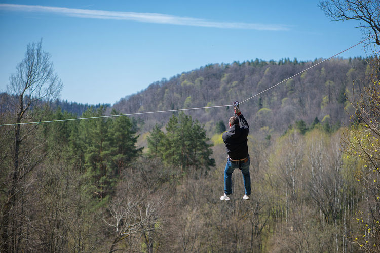 Rear View Of Man Hanging On Zip Line By Trees At Forest