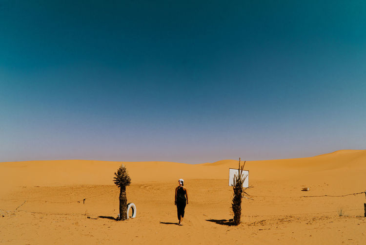 Rear view of woman walking on desert against sky