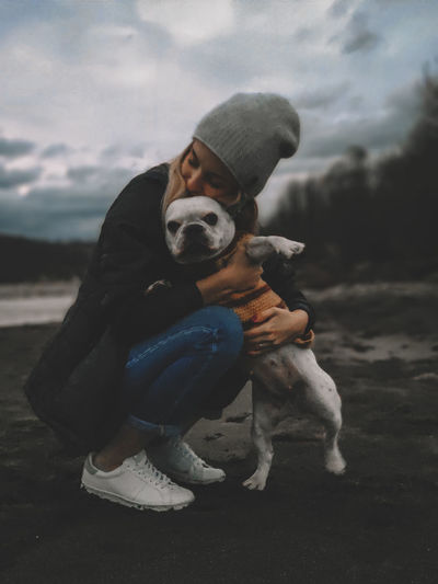 Woman embracing dog against sky