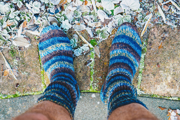 Low section of man in socks by frosted leaves on footpath
