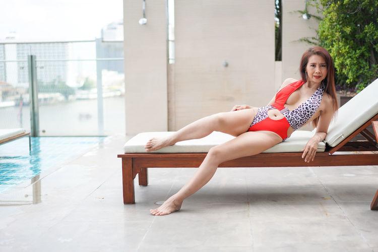 Portrait of woman sitting on swimming pool