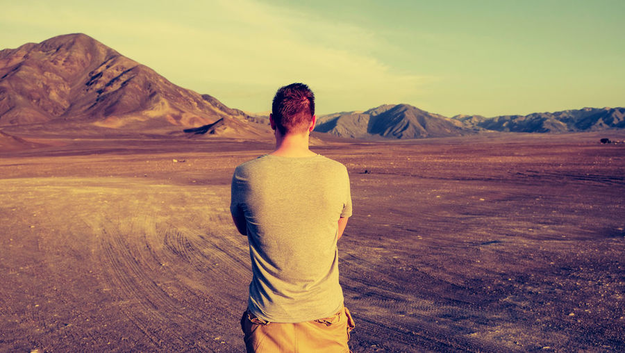 Rear View Of Man Standing On Barren Landscape Against Sky