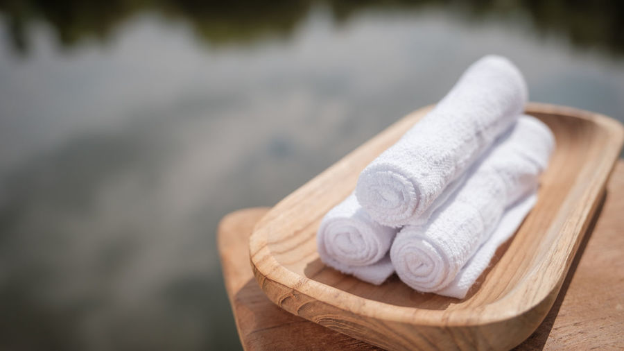 Close-Up Of Rolled White Towels In Wooden Tray By Lake