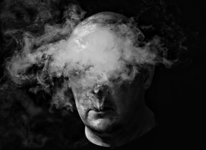 Cloud Vaping Man Black Background Portrait Human Face Headshot Ominous Front View Serious Close-up Surreal Spooky Mysterious