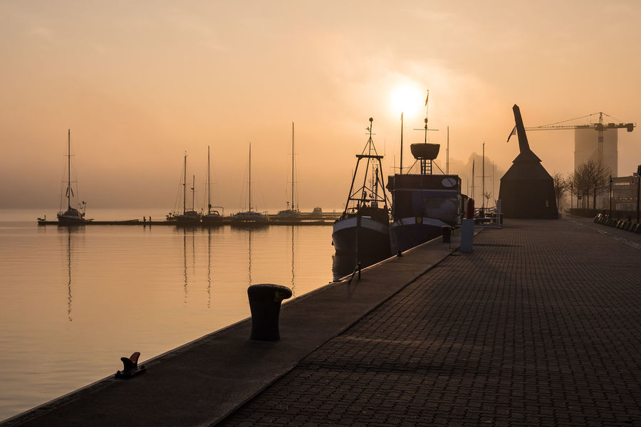 City port in Rostock, Germany. City Harbor Morning Rostock Harbor Jetty Mast Mode Of Transport Moored Nature Nautical Vessel Outdoors Pier Port Sailboat Sea Silhouette Sky Sunrise Sunup Town Transportation Travel Destinations Water Yacht