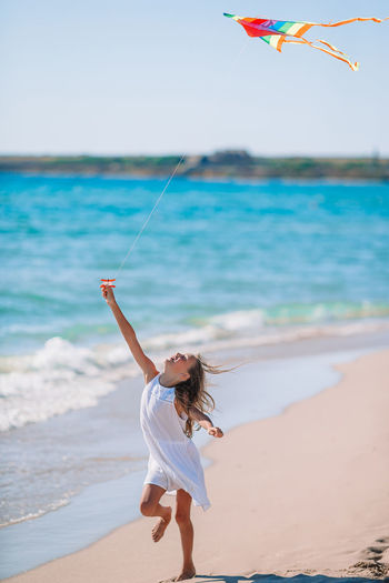 Smiling girl playing with kite on beach