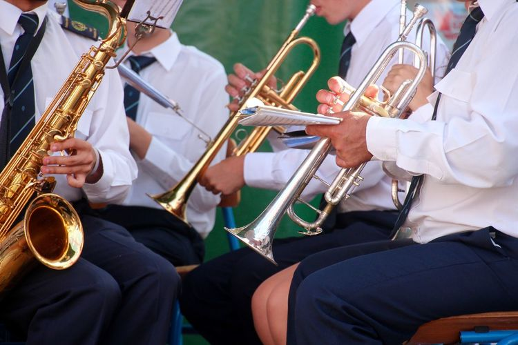 Midsection Of People Playing Trumpet At Ceremony