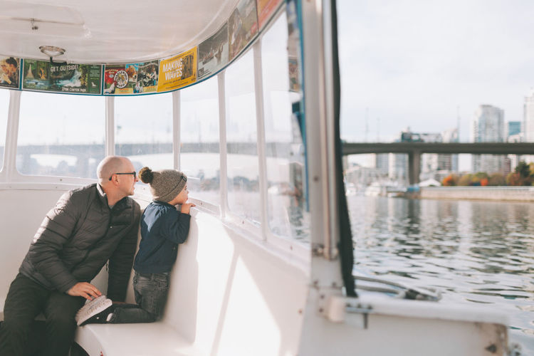 A father and son exploring a city by ferry boat. Family Father Son Boy Child Ferry Exploring Transit Transportation Boat Together Curious Ocean City