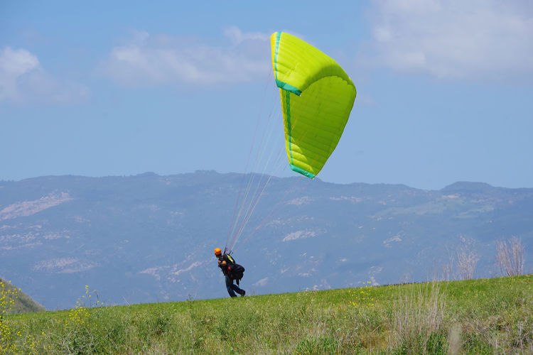 Person paragliding on field against sky