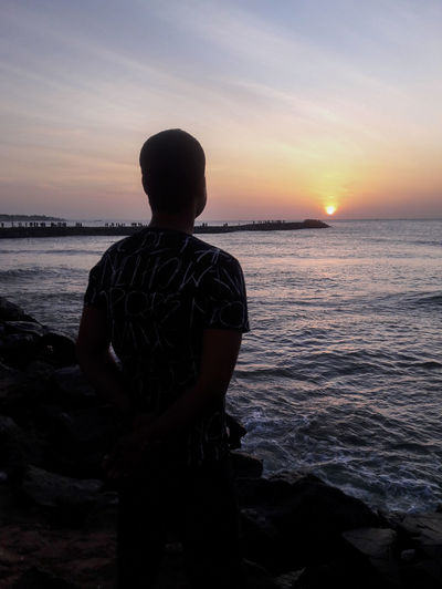 Rear view of man looking at sea against sunset sky