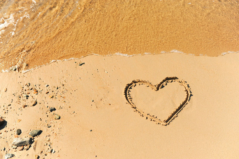 Painted heart on clean sand of beach and a wave of clear transparent water rolls, not glossy image