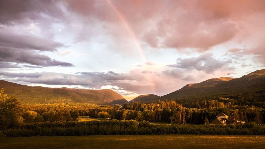 Scenic View Of Rainbow Over Mountains During Sunset