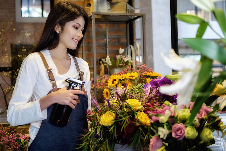 Florist spraying water on flowers at shop