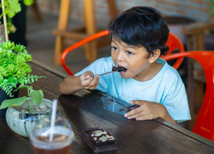 High angle view of boy eating dessert while sitting in restaurant