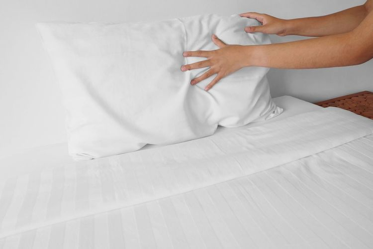 Cropped Image Of Hands Arranging Pillow At Home