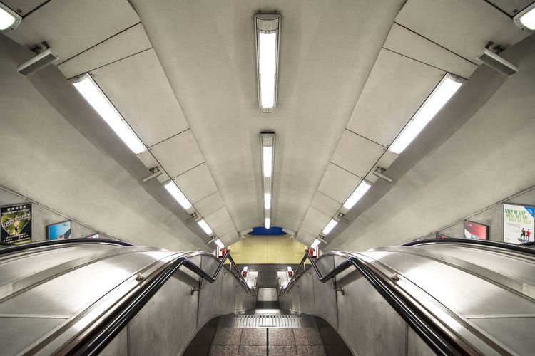 a view from the top of a staircase in a station of the London Underground system Central Line Jubilee Line London Trafalgar Transport For London Underground Victoria Line Architecture Built Structure Ceiling Day Futuristic Illuminated Indoors  Modern Piccadilly Real People Subway Subway Station Technology The Way Forward Transportation