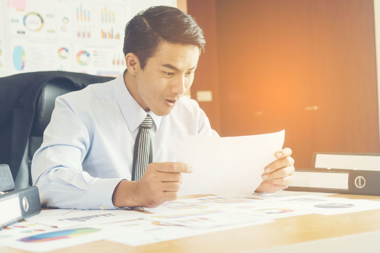Happy businessman reading document at desk in office