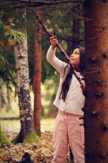 Girl Looking Up While Holding Stick