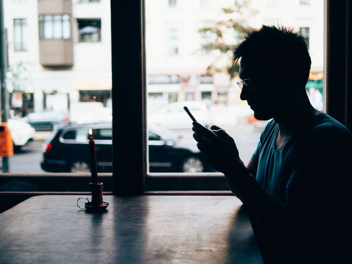 Side View Of Man Using Mobile Phone In Bar