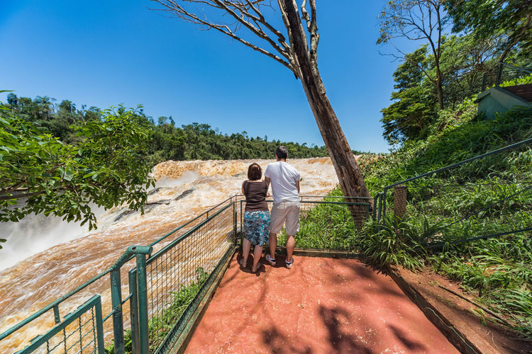 Rear view of couple standing by railing against waterfall