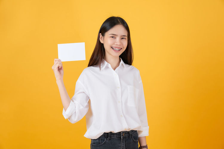 Portrait of smiling young woman against yellow background