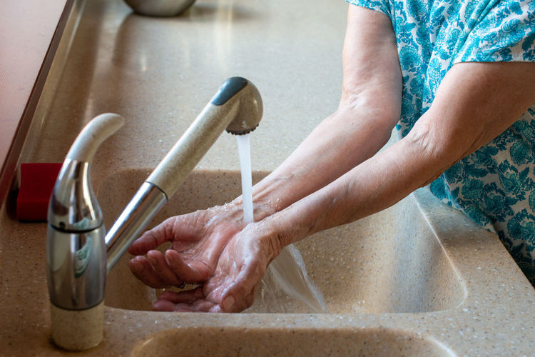 Senior woman's hands under cold running water. close up. how to stay cool in hot weather.