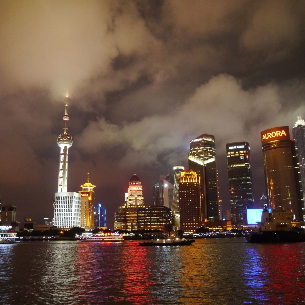 architecture, illuminated, building exterior, tall - high, night, city, built structure, sky, skyscraper, travel destinations, cloud - sky, water, tower, river, waterfront, cityscape, outdoors, no people, urban skyline, travel, modern, nautical vessel, nature