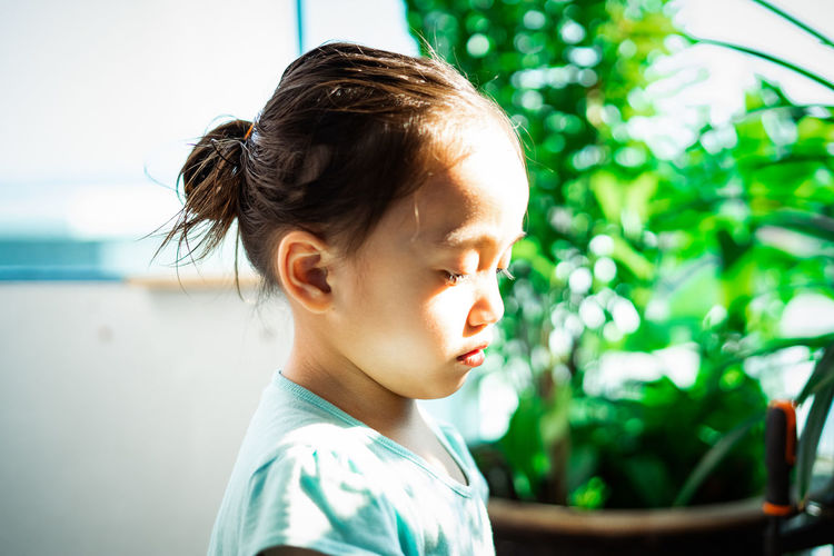 Side view of girl standing at home