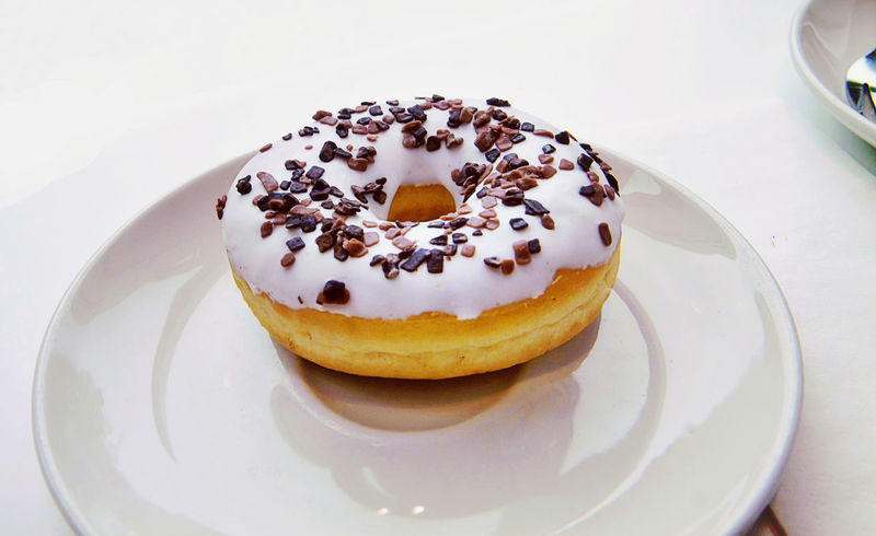 Delicious doughnut decorated with frosted vanilla glaze and chocolate chips Baked Cake Chocolate Sprinkles Close-up Day Dessert Donut Doughnut Food Food And Drink Freshness Glazed High Angle View Indoors  No People Pastry Plate Ready-to-eat Sweet Food Vanilla Frosting