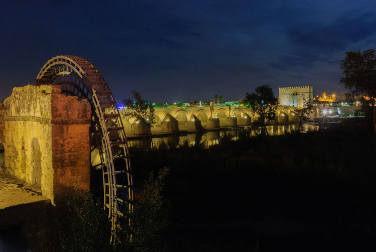 Cordoba Spain Mill Wheel Amusement Park Amusement Park Ride Architecture Arts Culture And Entertainment Building Building Exterior Built Structure City Cloud - Sky Dark Dusk Illuminated Nature Night No People Outdoors Sky Travel Destinations Tree Water