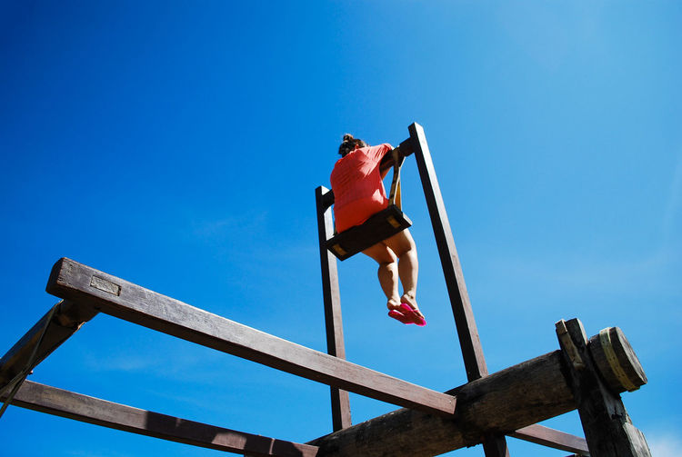 Low angle view of mid adult woman swinging against clear blue sky