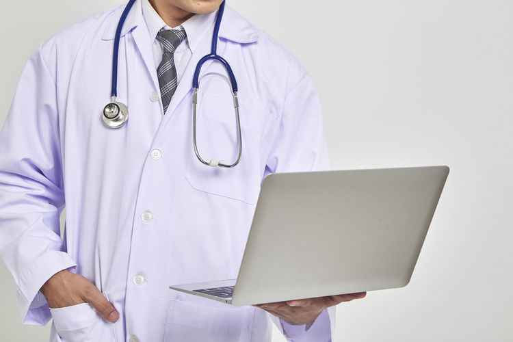 Midsection Doctor Holding Laptop Against White Background