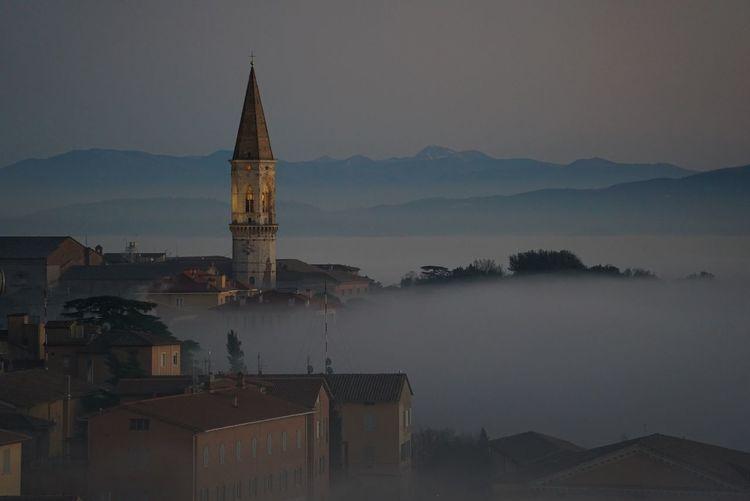 AERIAL VIEW OF CHURCH SPIRE AGAINST MOUNTAIN RANGE