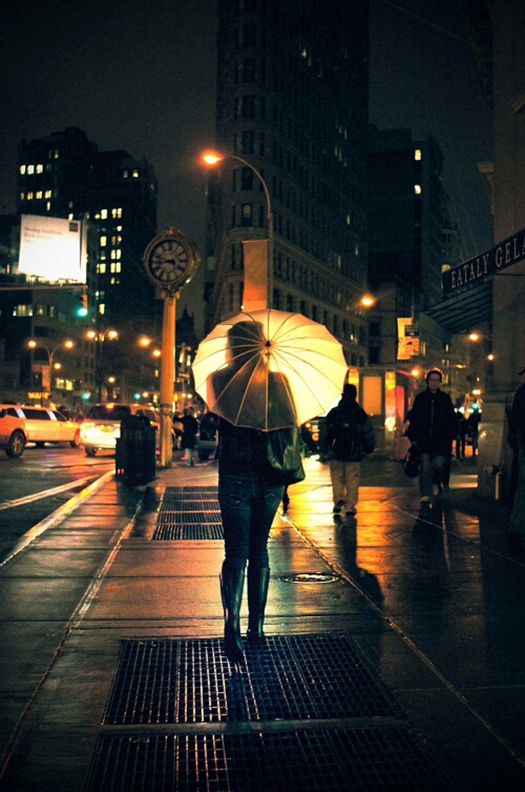 city, building exterior, illuminated, night, architecture, built structure, walking, city life, street, full length, men, city street, lifestyles, rear view, person, transportation, street light, zebra crossing